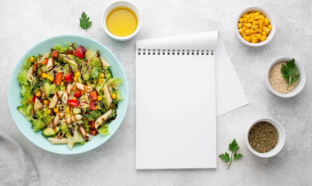 Top view pasta salad with balsamic vinegar and blank notepad