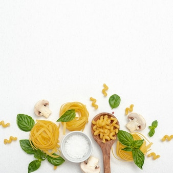 Top view of pasta and salt on plain background with copy space