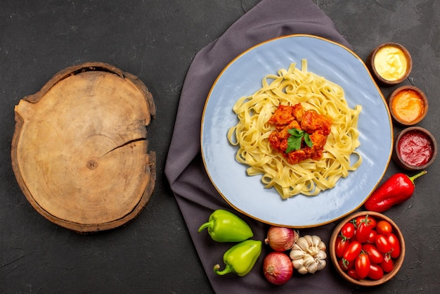 Vista dall'alto pasta su tovaglia piatto blu di appetitosa ciotola di pasta di salse di pomodori aglio cipolla peperone sulla tovaglia viola e tavola di legno sul tavolo