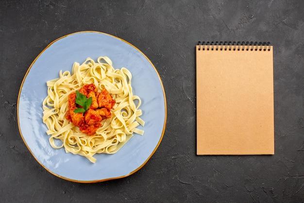 Вид сверху макароны с мясом синяя тарелка аппетитных макарон с соусом и мясом рядом с блокнотом с кремом на столе
