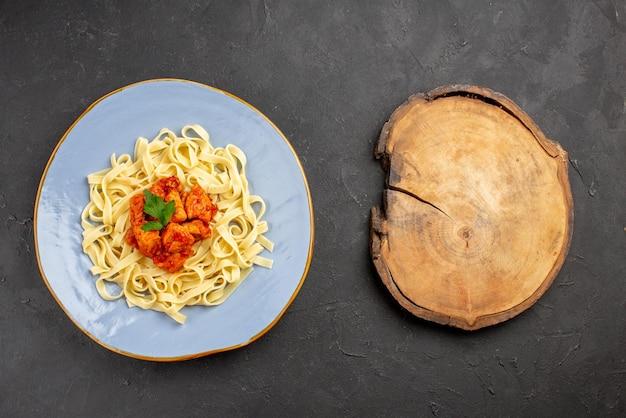 Вид сверху макароны с мясом синяя тарелка аппетитных макарон с соусом и мясом рядом с деревянной разделочной доской на столе