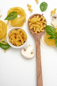 Top view of pasta and wooden spoon on plain background