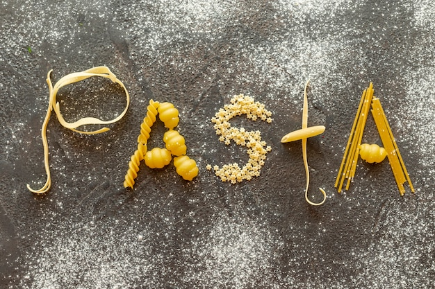 Top view of pasta word on plain background