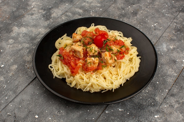 Top view pasta yellow cooked with chicken wings and tomato sauce inside black plate on the grey wooden rustic