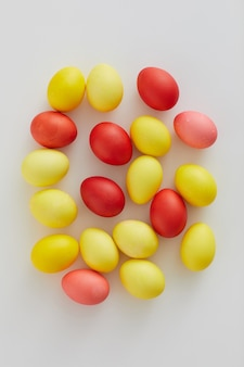 Top view of pastel colored easter eggs arraigned in minimal composition on white background, copy space