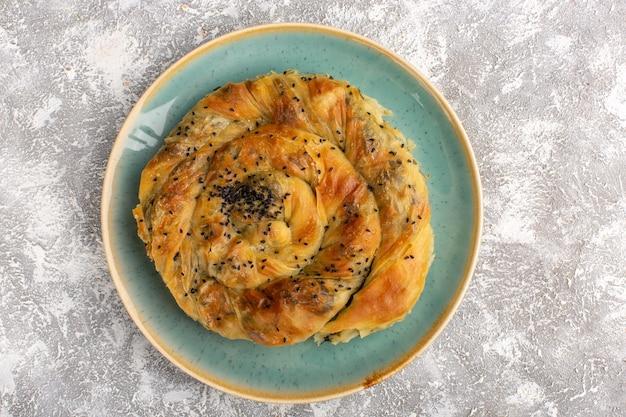 Vista dall'alto della pasticceria con farina di pasta deliziosa di carne all'interno del piatto sulla superficie chiara