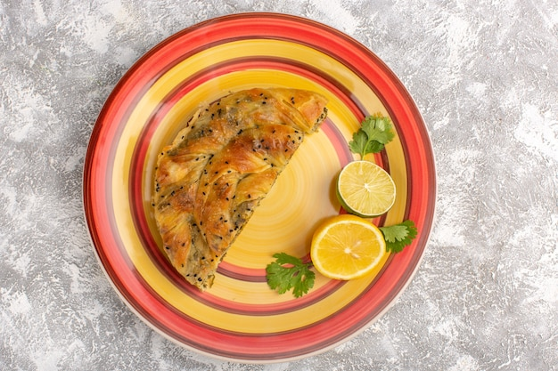 Top view of pastry with meat delicious dough meal inside plate sliced with lemon on light-white surface