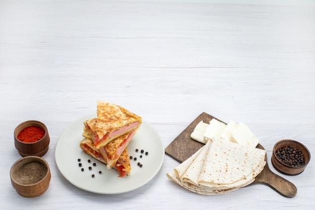 白い背景のペストリーフードミールランチの調味料と一緒にプレート内の野菜のトップビューペストリー