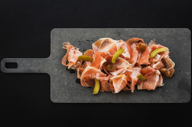 Top view of pata negra spanish ham with pickled cucumbers served on the board