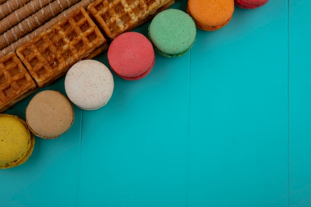 Top view of pattern of cookies and crispy sticks cakes on blue background