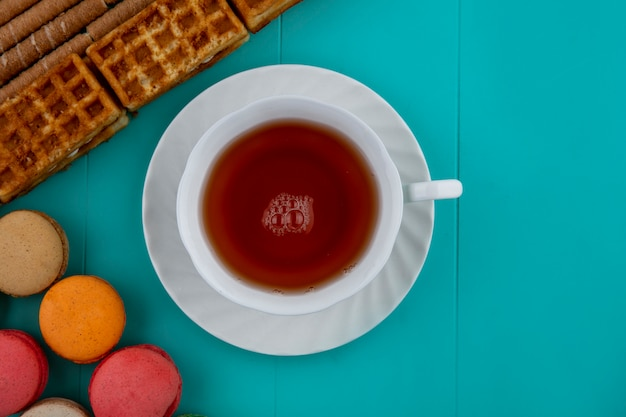 Top view of pattern of cookies and crispy sticks cakes with cup of tea on blue background with copy space