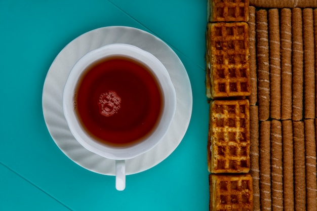 Top view of pattern of crispy sticks and cakes with cup of tea on blue background