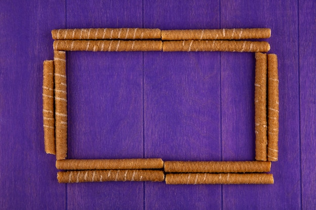 Top view of pattern of crispy sticks set in square shape on purple background with copy space