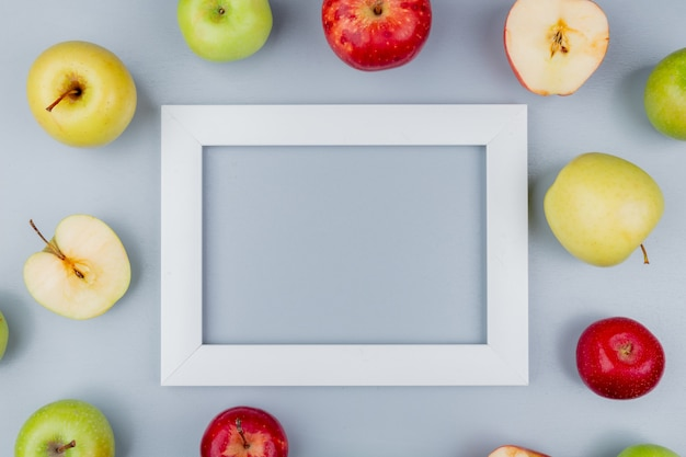 Top view of pattern of cut and whole apples around frame on gray background with copy space