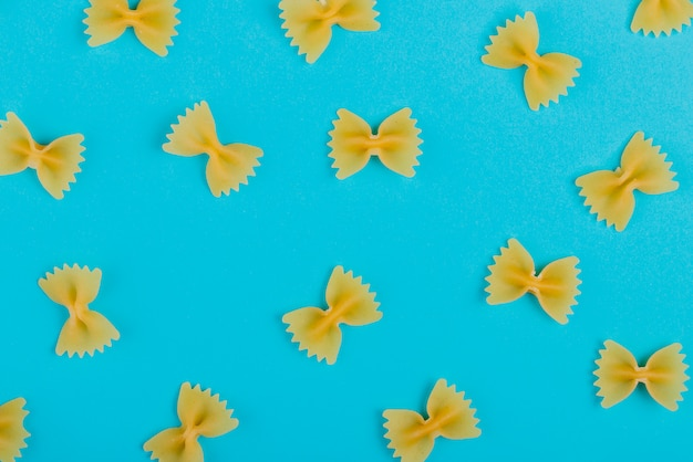 Top view of pattern of farfalle pasta on blue surface