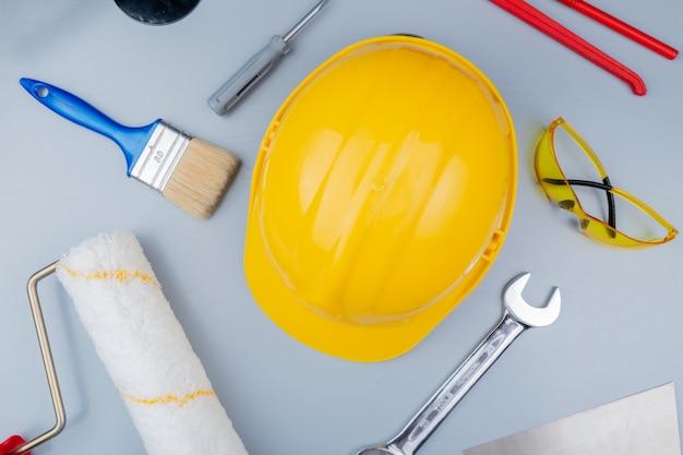 Vista dall'alto del modello dal set di strumenti di costruzione come cacciavite occhiali di sicurezza casco di sicurezza coltello stucco rullo di vernice pennello e chiave a forchetta su sfondo grigio