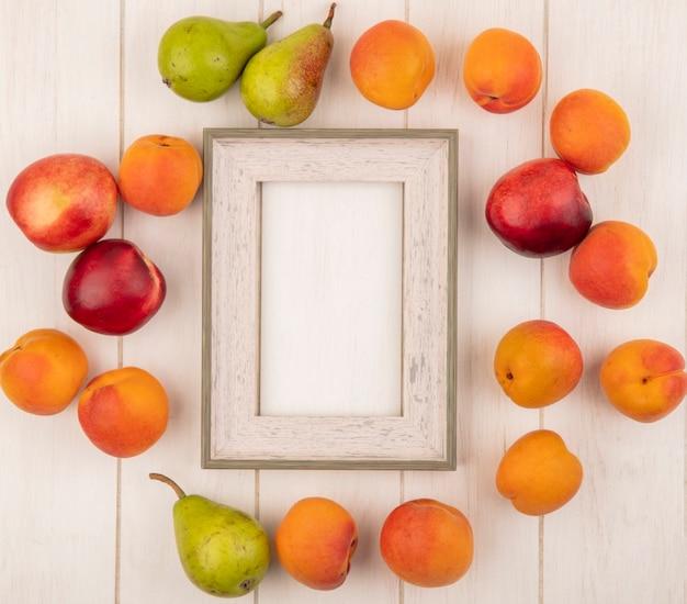 Vista dall'alto del modello di frutti come albicocche pesche e pere intorno al telaio su sfondo di legno con copia spazio
