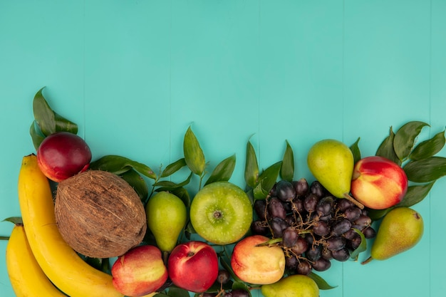 Top view of pattern of fruits as coconut pear peach grape apple banana with leaves on blue background with copy space