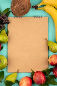 Top view of pattern of fruits as coconut pear peach grape banana apple around note pad on blue background with copy space