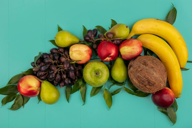 Top view of pattern of fruits as coconut pear peach grape banana apple with leaves on blue background