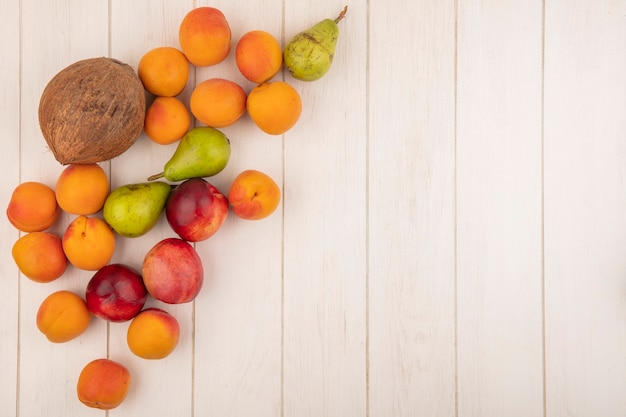 Top view of pattern of fruits as peach apricot pear coconut on wooden background with copy space