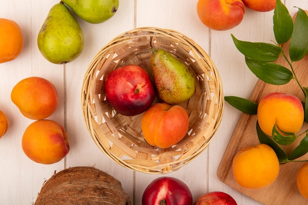 Top view of pattern of fruits as peach pear apricot in basket and peaches on cutting board with pears and coconut on wooden background