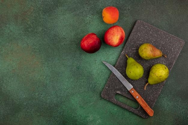 Vista dall'alto del modello di frutta come pere con coltello sul tagliere e pesche albicocca su sfondo verde con copia spazio