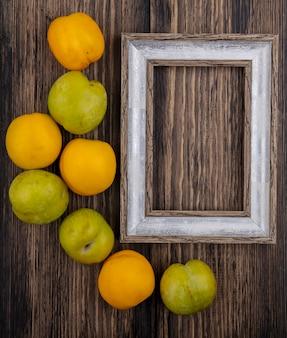 Vista dall'alto del modello di frutti come pluots e nectacots con cornice su sfondo di legno con spazio di copia