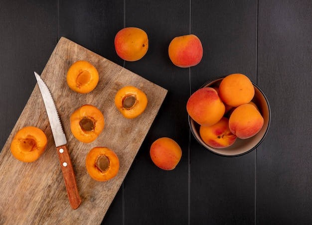 Top view of pattern of half cut apricots with knife on cutting board and whole ones in bowl and on black background