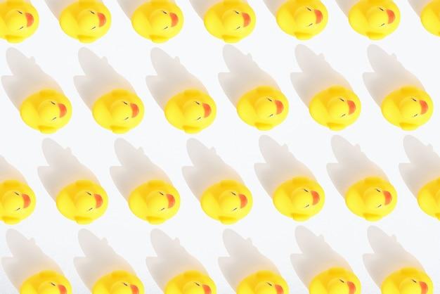 Узор вид сверху игрушечных желтых утят на белом фоне с тенью