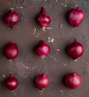 Top view of pattern of red onions on maroon background with copy space