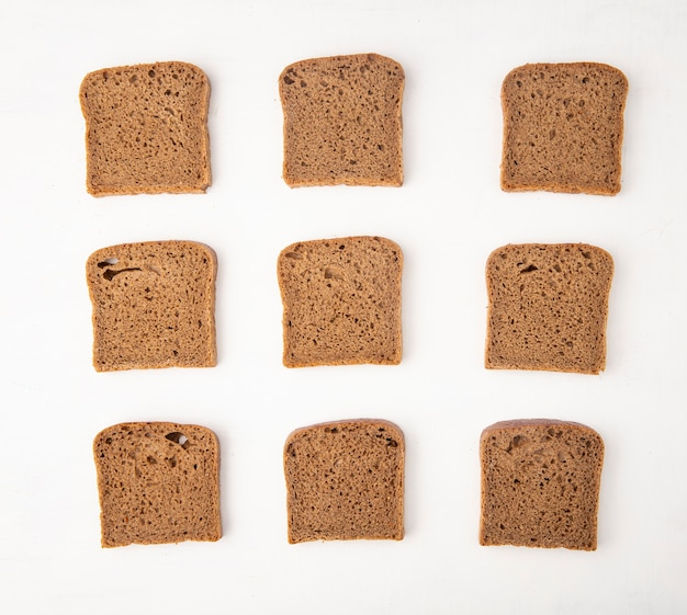 Top view of pattern of rye bread slices on white background