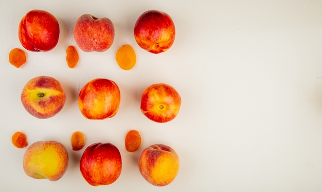 Top view of pattern of sliced and whole peaches on left side and white surface with copy space