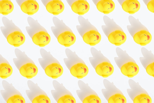 Top view pattern of toy yellow ducklings on white background with shadow