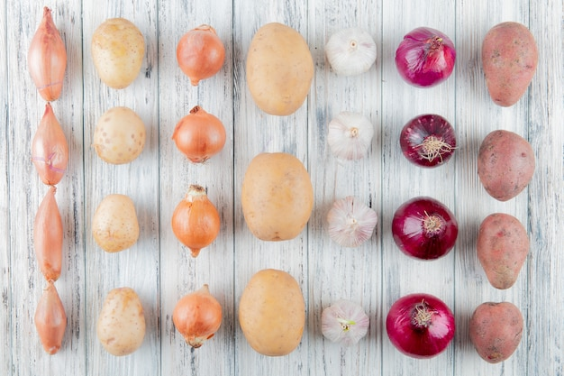 Top view of pattern of vegetables as shallot onion potato garlic on wooden background