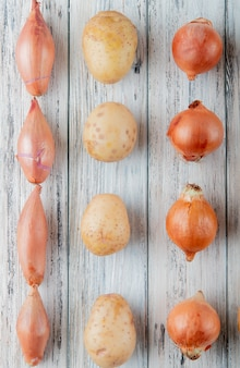 Top view of pattern of vegetables as shallot potato onion on wooden background