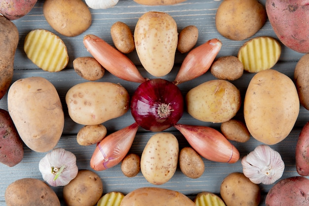 Top view of pattern of vegetables as sliced and whole potato shallot garlic and onion on wooden background