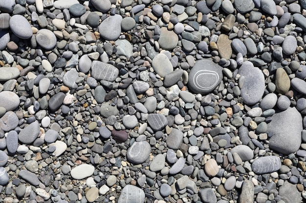 Top view of patterned stones on pebble shore in flat lay