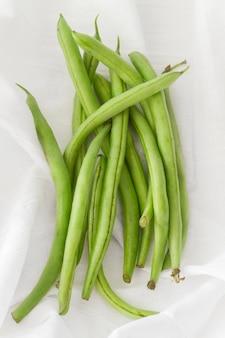 白い布の上のトップビューエンドウ豆の鞘