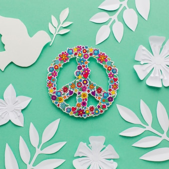 Top view of peace sign with paper dove and leaves