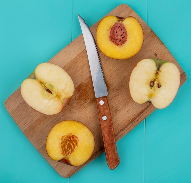 Top view of peach halves with apple halves on a blackboard with a knife on a light blue surface