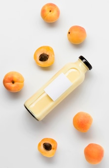Top view of peach juice bottle with fruits