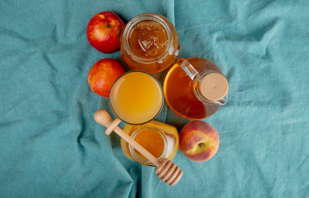 Top view of peach juice in a glass and glass jars with honey and peach jam and fresh sweet nectarines on blue