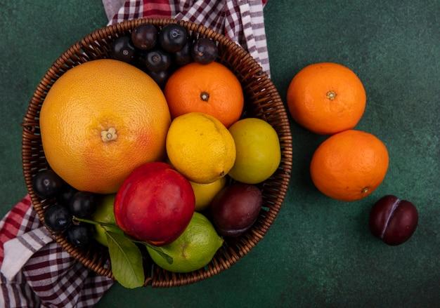 Vista dall'alto pesca con prugne ciliegia arance limoni limette e pompelmo in un cesto con un asciugamano a scacchi su uno sfondo verde