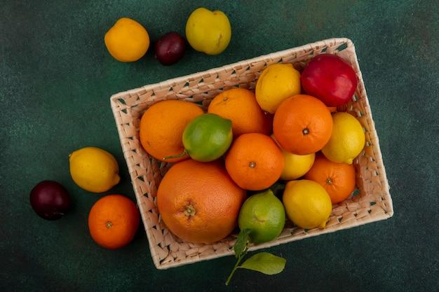 Vista dall'alto pesca con limoni limette prugne pompelmo e arance in un cesto su uno sfondo verde