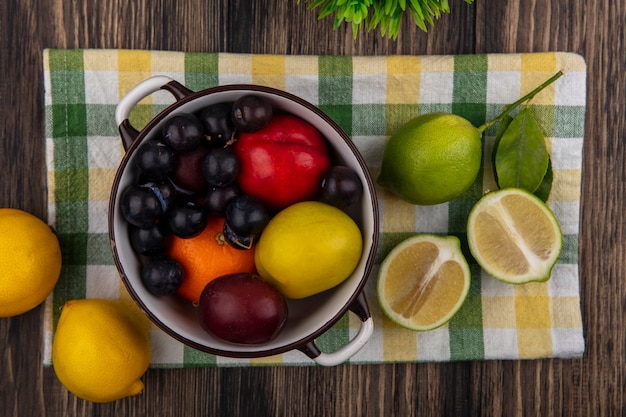 Top view peach with orange  plum and cherry plum in a saucepan with limes and lemons on a checkered towel on a wooden background