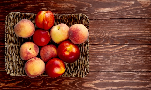 Top view of peaches in basket plate on left side and wooden surface with copy space