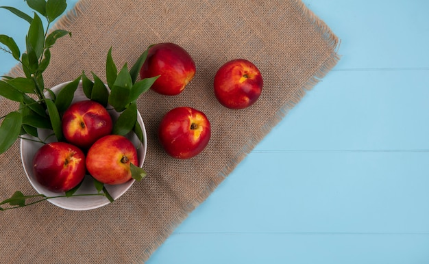 Top view of peaches in a bowl with leaf branches on a beige napkin on a light blue surface