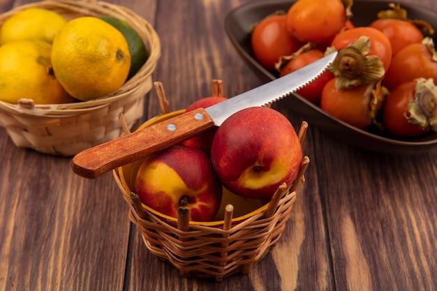Vista dall'alto di pesche su un secchio con coltello con mandarini con cachi su una ciotola su una superficie di legno