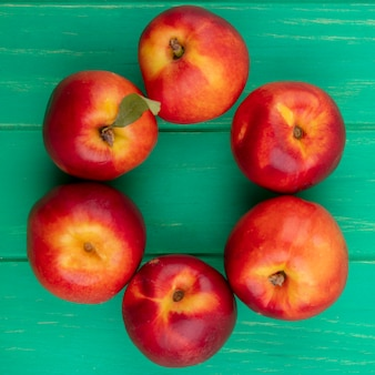 Top view of peaches on a green surface